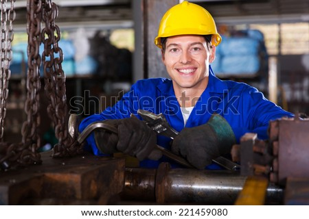 portrait of industrial manual worker in workshop - stock photo