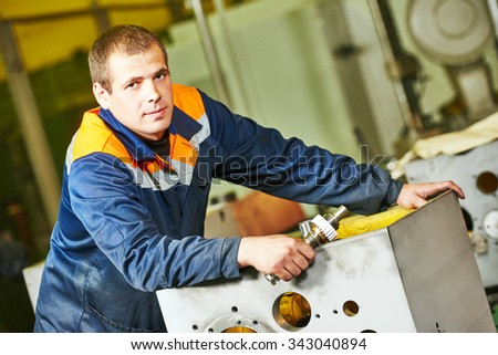 Portrait of industrial worker assembling the reduction gear box on production line manufacturing workshop - stock photo