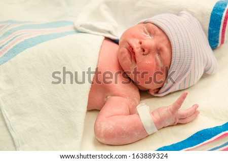 Portrait of infant with eye gel applied moments after delivery at hospital - stock photo