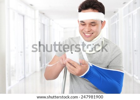 portrait of injured young man look happy play smartphone - stock photo