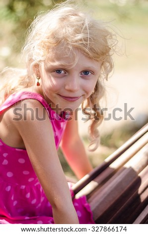 portrait of innocent adorable little child with long blond hair - stock photo