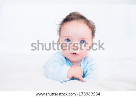 Portrait of innocent baby boy with blue eyes lying in bed - stock photo