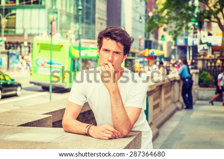 Portrait of Innocent Young College Student. Wearing white T shirt, hand touching his lips, a young European guy standing by stone fence on street in New York, watching, thinking. Instagram effect. - stock photo