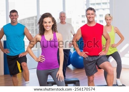 Portrait of instructor with fitness class performing step aerobics exercise in gym - stock photo