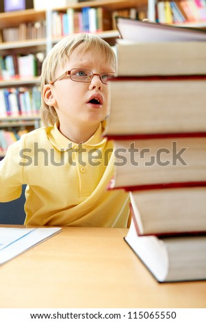 Portrait of interested schoolkid looking at stack of books in the library