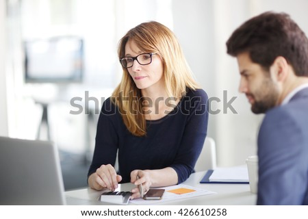 Portrait of investment advisor businesswoman consulting with young financial businessman. - stock photo