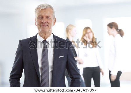 Portrait of investment advisor standing at office background with business team.