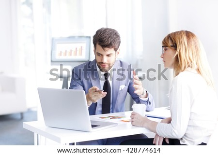 Portrait of investment agent consulting with his client while sitting at office and using laptop.