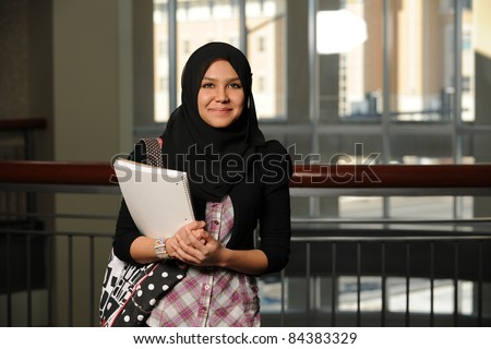 Portrait of Islamic young woman holding books indoors