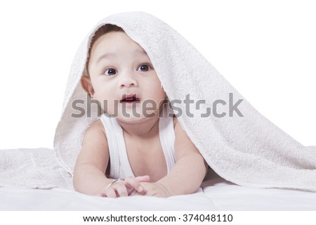 Portrait of joyful baby crawling under a towel, isolated on white background - stock photo