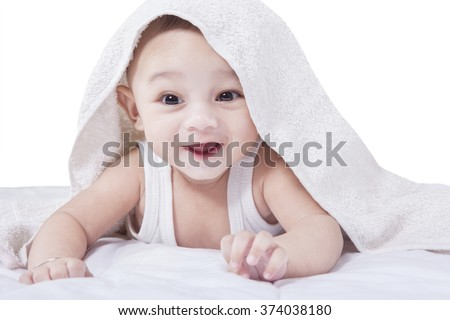 Portrait of joyful baby lying under a towel while laughing at the camera, isolated on white - stock photo