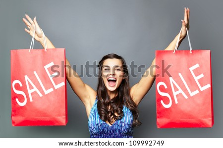 Portrait of joyful brunette with sale paperbags looking at camera