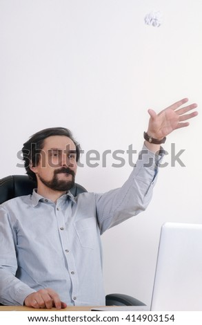portrait of joyful businessman throwing crumpled paper at the business office; business concept; business work - stock photo