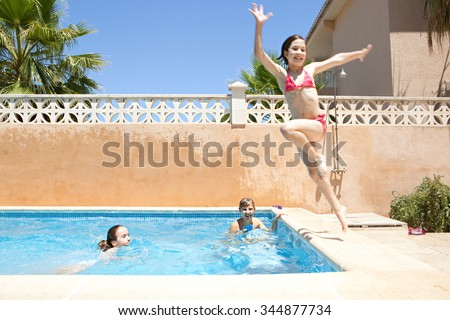Portrait of joyful child boy having fun by swimming pool in home garden summer holiday, smiling with wet hair in swimwear outdoors playing with water pistol. Active kids lifestyle exterior vacation. - stock photo