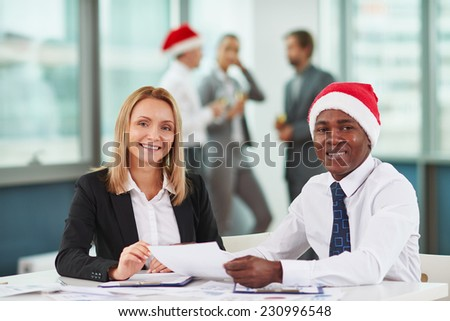 Portrait of joyful colleagues looking at camera at workplace on background of their business partners - stock photo
