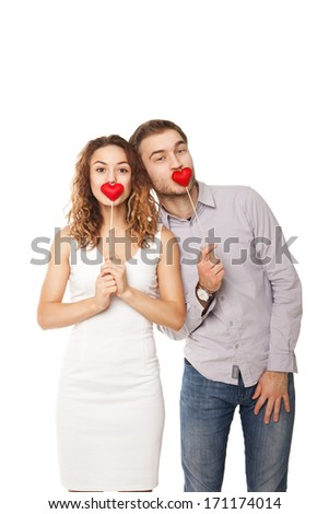 Portrait of joyful couple holding red hearts and laughing isolated on white - stock photo