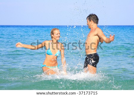 Portrait of joyful couple of people having fun in the sea and laughing