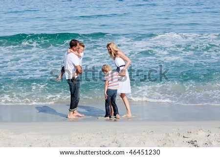 Portrait of joyful family sitting on the sand at the beach