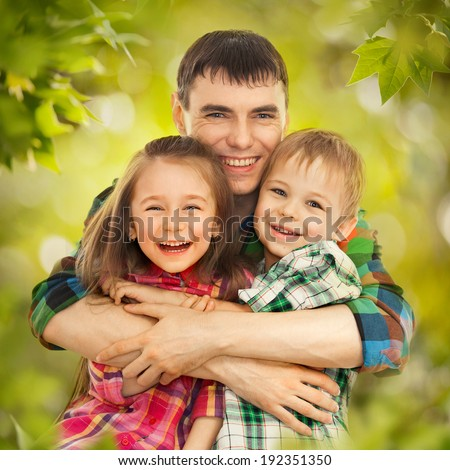 Portrait of joyful father hugging his son and daughter. Fathers day, family holiday, vacation