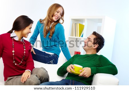 Portrait of joyful friends chatting at home - stock photo