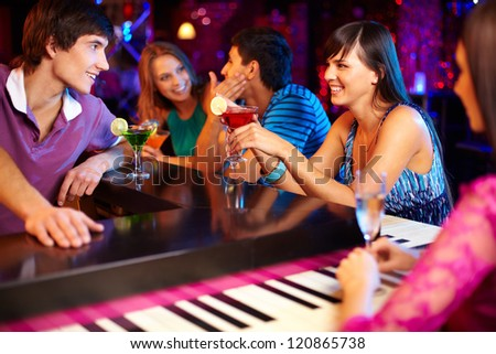 Portrait of joyful friends having party in the bar - stock photo