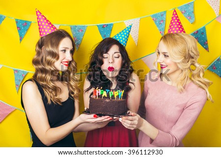 Portrait of joyful friends toasting and looking at camera at birthday party. Attractive friends celebrating a birthday. Smiling girls - stock photo