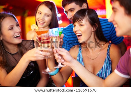 Portrait of joyful friends toasting at birthday party with focus on two happy girls - stock photo