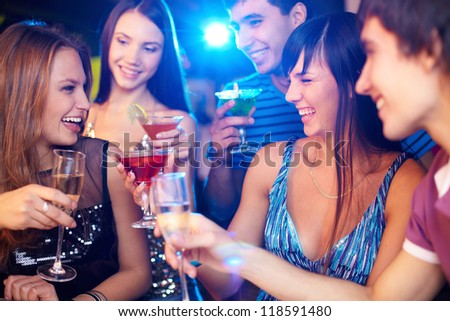Portrait of joyful friends toasting at birthday party with focus on two laughing girls - stock photo
