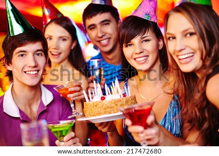 Portrait of joyful friends with birthday cake and drinks looking at camera at party