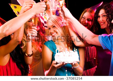 Portrait of joyful girl holding birthday cake surrounded by her friends with flutes - stock photo