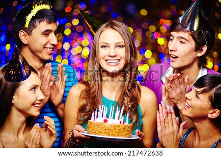 Portrait of joyful girl with birthday dessert looking at camera with friends near by - stock photo