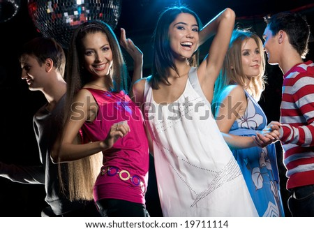 Portrait of joyful girls laughing while dancing at disco with their boyfriends
