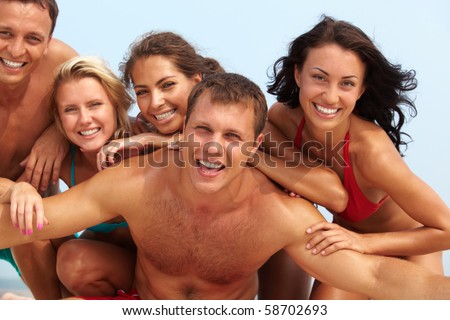 Portrait of joyful guy and happy girls in bikini on background looking at camera on summer vacation - stock photo