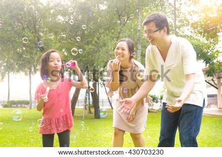 Portrait of joyful happy Asian family playing bubbles together at outdoor park during summer sunset. - stock photo