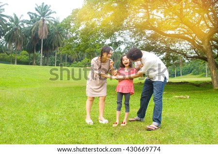 Portrait of joyful happy Asian family playing together at outdoor park during summer sunset. - stock photo