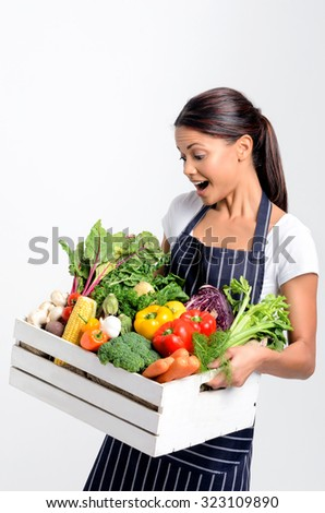 Portrait of joyful hispanic woman chef holding a crate full of fresh organic vegetables on grey background, promoting eating seasonally and sourcing from local producers