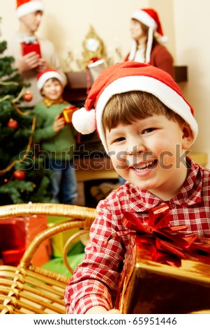 Portrait of joyful little boy holding present on the background of his relatives - stock photo