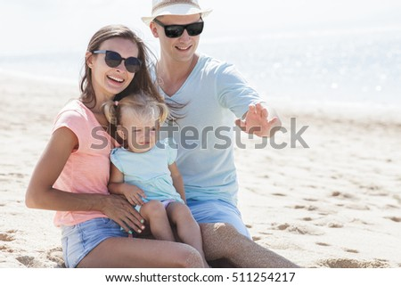 portrait of joyful little family having fun together on the beach