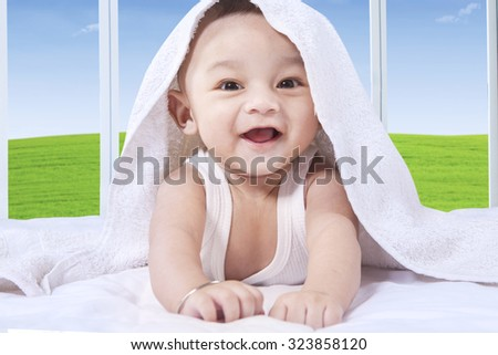 Portrait of joyful male baby playing under a white towel on the bedroom and laughing on the camera - stock photo