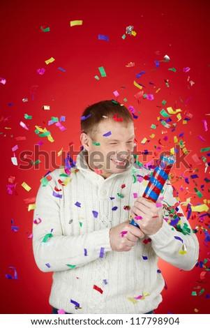 Portrait of joyful man in white pullover having fun with confetti cracker - stock photo