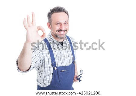 Portrait of joyful mechanic with silver wrench making ok gesture with advertising area isolated on white background - stock photo