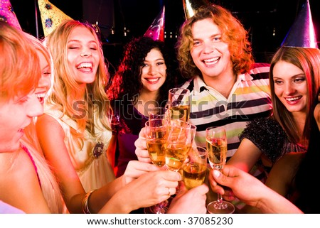 Portrait of joyful people with flutes of champagne toasting at birthday party