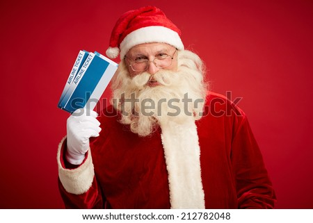 Portrait of joyful Santa with airline tickets looking at camera