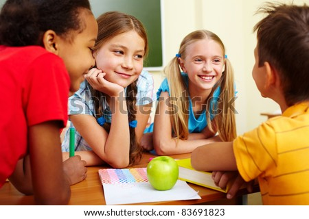 Portrait of joyful schoolchildren chatting in classroom