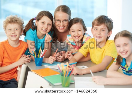 Portrait of joyful schoolkids and successful teacher looking at camera - stock photo