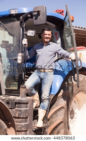 portrait of joyful smiling mature male farmer near huge tractor