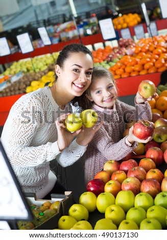 Portrait of joyful smiling mother and little daughter buying ripe apples at the market. Focus on woman