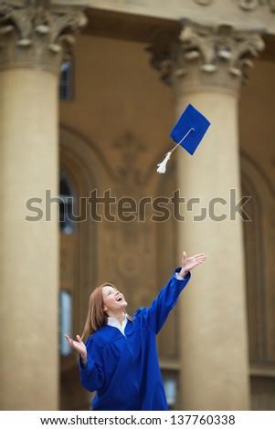 Portrait of joyful student throwing graduation hat - stock photo