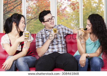 Portrait of joyful teenagers drinking champagne on sofa with autumn background on the window - stock photo