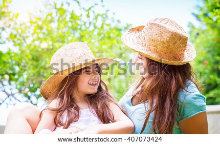 Portrait of joyful young mother with cute cheerful daughter wearing same straw hats and playing outdoors, laughing and looking on each other, portrait of a happy family enjoying life - stock photo